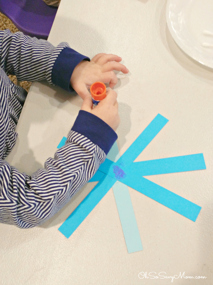 3 year old making a winter Snowflake craft in preschool